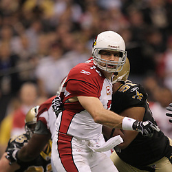 16 January 2010:  Arizona Cardinals quarterback Kurt Warner (13) is hit by New Orleans Saints defensive end Will Smith (91) as he throws the ball during a 45-14 win by the New Orleans Saints over the Arizona Cardinals in the 2010 NFC Divisional Playoff game at the Louisiana Superdome in New Orleans, Louisiana.