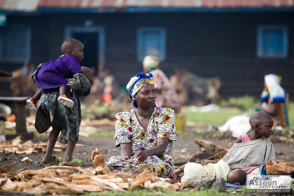 An internally displaced woman sits on the ground with her children outside the Kanyaruchinya school in the town of Kibati, on the outskirts of Goma, Eastern Democratic Republic of Congo on Friday December 12, 2008. Classes stopped in the school - normally attended by 400 children - when people displaced by recent fighting found refuge inside the school buildings.