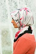 Turkey, Istanbul, A muslim girl near a fountain.