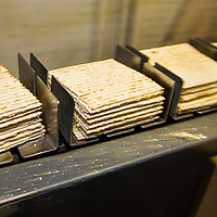 Making Kosher for Passover matzoh at Streit's Matzoh, Lower East Side, NYC. By Jewish law, to keep matzoh fit for use during Passover one must complete the entire matzoh-making process - from the time the grain comes into contact with the water up to and including the completion of the baking of the matzoh - within 18 minutes. Matzoh is taken from the oven and sorted into stacks of 11 pieces, which are placed in wire baskets. The baskets will carry the pre-sorted matzoh to the packaging room where each stack will fill an 11 0z. box.