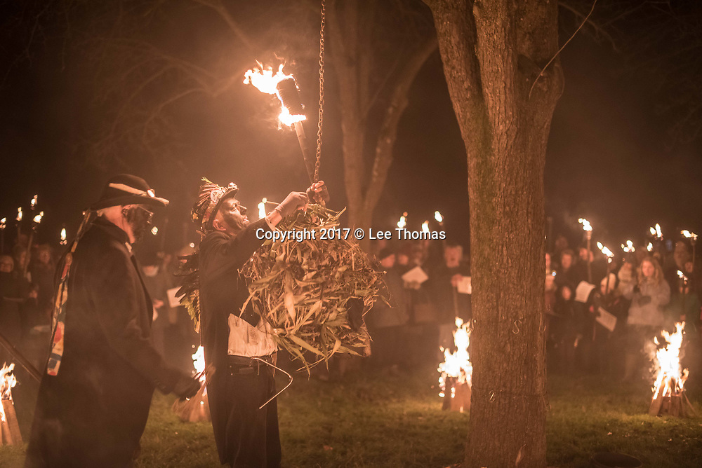 Much Marcle, Herefordshire, UK. 6th January 2018. Pictured:  Morris men perform the ceremony of  Burning the Bush, which  may symbolise the returning sun and lengthening days. / Hundreds of people both young and old gathered at the Westons Cider Mill and adjoining orchard to take part in the traditional Wassail ceremony. The event at Much Marcle in Herefordshire was attended by the Silurian morris side who entertained the crowd with witty repartee, raucous dancing and music. According to their website, the true origins of blackened faces are lost to history, but are widely believed to be simply a form of disguise, possibly to overcome the oppressive anti-begging laws of the 17th century, and the eternal embarrassment of being a morris man. The orchard-visiting wassail refers to the ancient custom of visiting orchards in cider-producing regions of England, reciting incantations and singing to the trees to promote a good harvest for the coming year.   // Lee Thomas, Tel. 07784142973. Email: leepthomas@gmail.com  www.leept.co.uk (0000635435)