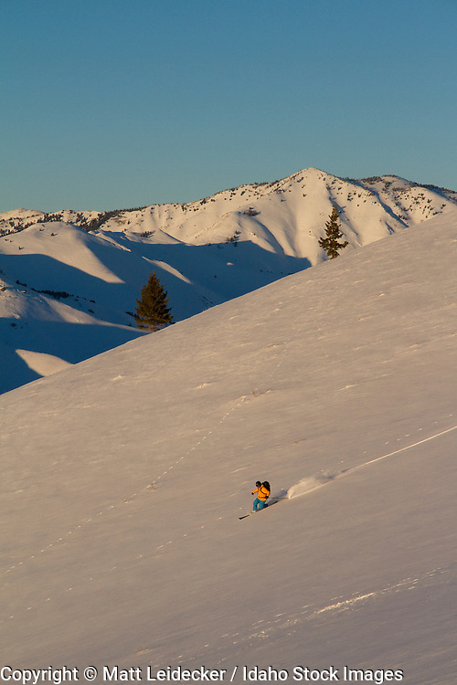 Backcountry skiier skiing in the sunset light in the pioneer mountains.  Johnstone Peak (9949 feet) in the background.