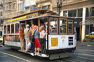 Passengers hang off the side of a Cable Car, San Francisco, California