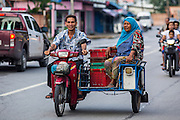 25 OCTOBER 2012 - PATTANI, PATTANI, THAILAND:   A Muslim family on a motorcycle in Pattani, Thailand. More than 5,000 people have been killed and over 9,000 hurt in more than 11,000 incidents, or about 3.5 a day, in Thailand's three southernmost provinces and four districts of Songkhla since the insurgent violence erupted in January 2004, according to Deep South Watch, an independent research organization that monitors violence in Thailand's deep south region that borders Malaysia.   PHOTO BY JACK KURTZ