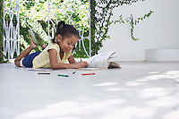 Girl (5-6 years) lying on porch and drawing