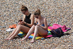 © Licensed to London News Pictures. 19/05/2014. Brighton, UK. 2 woman sunbathing on Brighton beach. The hot weather is continuing with record temperatures all around the UK. The beach in Brighton attracted hundreds of sun seekers. Photo credit : Hugo Michiels
