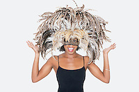 Portrait of happy African American woman wearing a feather mask over gray background