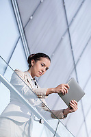 Beautiful young businesswoman using tablet computer at office railing