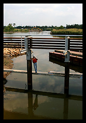 1 June, 2006. Lakeview, New Orleans, Louisiana. First day of hurricane season. Kewit contractors of the Gilbert Southern Group working for the US Army Corps of Engineers work on the $41.5 million Orleans Canal Interim Closure structure. The structure, designed to prevent water build up in the canal during hurricane storm surges is almost complete. A worker talks on his cell phone amidst the structure. The pumping capacity has yet to match that of pre hurricane Katrina levels, potentially leaving the affluent Lakeview neighbourhood unprotected once again.
