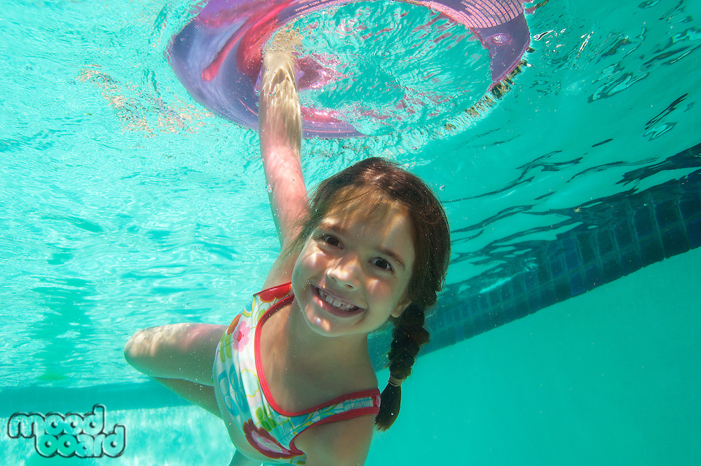 Girl holding inflatable raft underwater in swimming pool, portrait