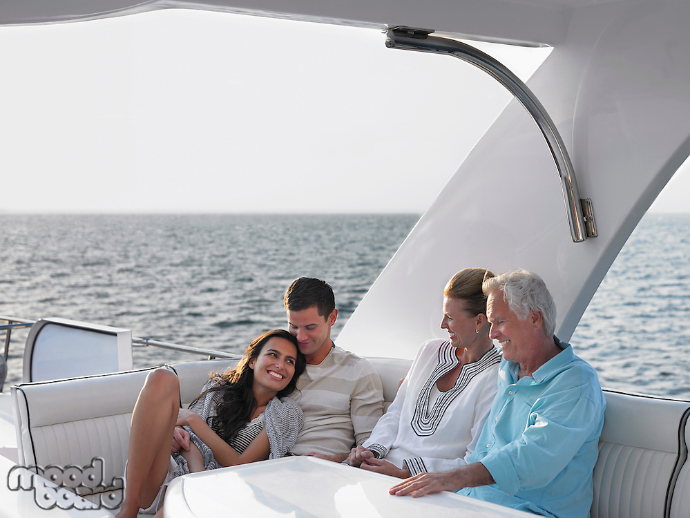 Young and middle-aged couple relaxing on yacht