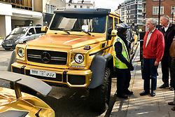 © Licensed to London News Pictures. 31/03/2016. London, UK. A fleet of supercars including a six-wheel £370,000 Mercedes G63 covered in gold chrome wrap receives a parking ticket by an attendant in Knightsbridge, London on Wednesday, 31 March 2016. Cars are believed to be owned by Saudi billionaire Turki Bin Abdullah .Photo credit: Ray Tang/LNP
