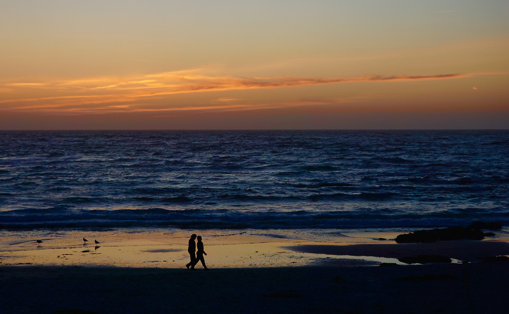 A couple walks on Asilomar State Park, CA, beach at sunset,