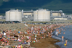 Busy beach at Prigorodnoye near Korsakov on Sakhalin Island with LNG tanks built by Shell 2008