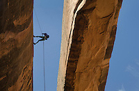 Climber rapelling down a cliff adjacent to Morning Glory Arch, near Moab Utah