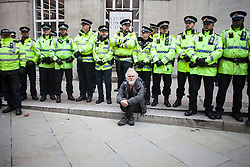 © Licensed to London News Pictures. 04/10/2017. Manchester, UK.  A protester sits in front of a line of police officers during the demonstration on the final day of the Tory Party Conference. The protest was as part of the Take Back Manchester festival to protest the conference taking part in the city.  Photo credit: Steven Speed/LNP