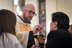 20 April 2019, Jerusalem: Father Bernard distributes bread during Holy Communion, as the congregation gathers for Holy Saturday service at Saint James' Church in Beit Hanina, Jerusalem.