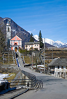 Ticino, Southern Switzerland. The pretty pink village church in Maggia against the alpine backdrop.