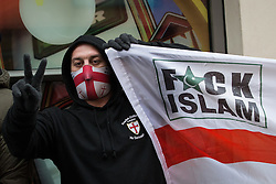 "© Licensed to London News Pictures . 04/01/2014 . London , UK . A demonstration by the English Defence League on Edgware Road against a planned anti-gambling demonstration by "" The Sharia Project "" today (4th January 2014) . An EDL supporter holds a flag with a St George's Cross and the words Fuck Islam . The Sharia Project opposes democracy and wish for a global caliphate governed by Sharia law . Photo credit : Joel Goodman/LNP"