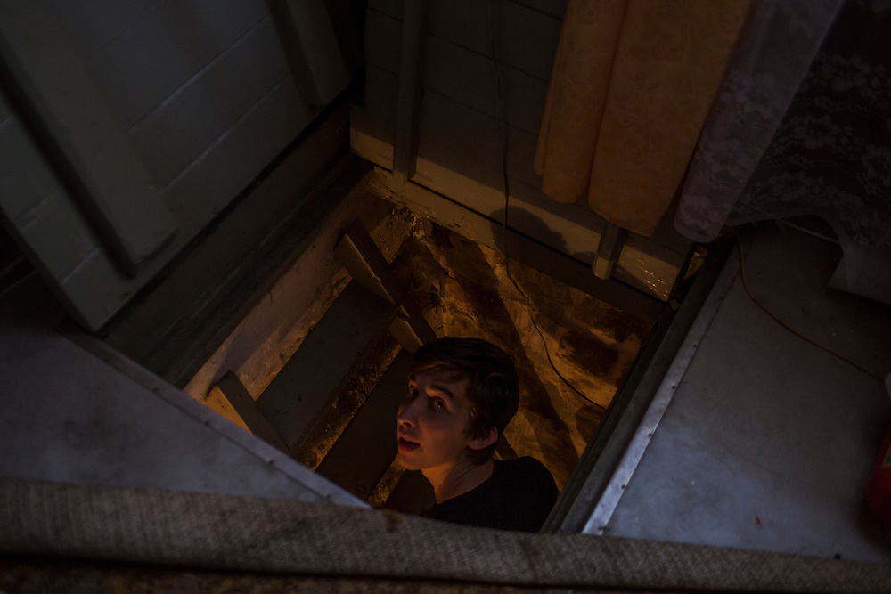 LUHANSK, UKRAINE - MARCH 16, 2015: Pavel Pavlov climbs into the basement where he and friend Aleksandr Kryukov hid from shelling in the house where Kryukov lives with his grandmother in Luhansk, Ukraine. The two have created a series of popular YouTube videos involving scientific experiements. CREDIT: Brendan Hoffman for The New York Times