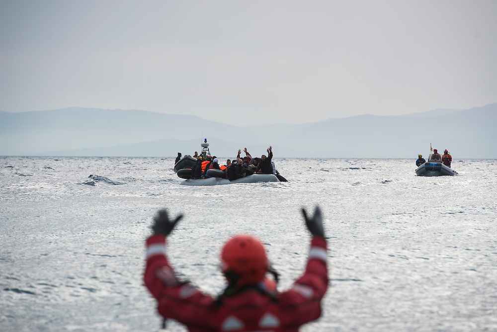 Volunteer rescue workers direct a refugee boat as it arrives on Lesbos Island on  <br />