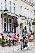 Cyclist cycling past al fresco diners at restaurant in Kerk Straat, Damme, West Flanders, Belgium