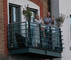 © Licensed to London News Pictures. 09/04/2020. London, UK. A couple clap on their balcony in Wandsworth. Millions of Brits take to their balconies and doorsteps around the country to applaud the NHS and frontline workers this evening as Prime Minister Boris Johnson leaves ICU department at St Thomas's Hospital as the coronavirus crisis continues. Photo credit: Alex Lentati/LNP