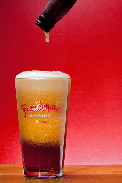 The last drop of beer hangs from the bottle with the head forming in the Frankenmuth Brewing Co. glass below
