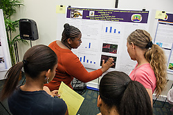 """Annesha King explains her research on """"Age-related changes in glial cell line-derived neurotrophic factor"""" to organizing committee person Dr. Teresa Turner and undergraduate students Jenelle Henry (L) and Jericea Bassue (R). Fourteenth Annual Fall Research Symposium, St. Thomas Campus, College of Science & Mathematics.  23 September 2012. Administration and Conference Center (ACC).  University of the Virgin Islands.  © Aisha-Zakiya Boyd"""