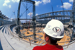 Stock photo of a man standing at the construction site of Houston's Reliant Stadium near downtown Houston Texas