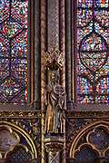 Detail of pillar made of three small columns on each side of a larger central column decorated with golden French Fleur de lys and flanked by a statue of apostle, nave of the upper chapel of La Sainte-Chapelle (The Holy Chapel), 1248, Paris, France. La Sainte-Chapelle was commissioned by King Louis IX to house his collection of Passion Relics, including the Crown of Thorns. The Sainte-Chapelle is considered among the highest achievements of the Rayonnant period of Gothic architecture. Picture by Manuel Cohen