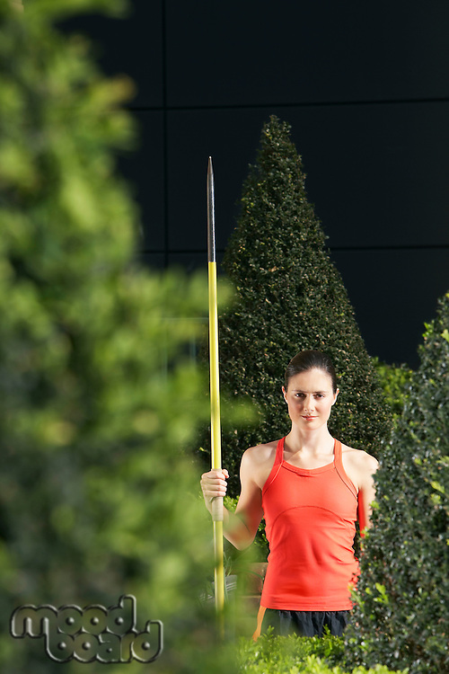 Woman holding javelin standing in landscaped garden portrait