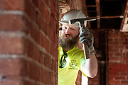 NWR Construction employee Chad Case chips out old pieces of masonry in preparation for reframing a window.