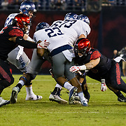 18 November 2017:  The San Diego State football team hosts Nevada Saturday night. San Diego State Aztecs safety Trey Lomax (3) and defensive lineman Sergio Phillips (65) combine on a tackle of Nevada Wolf Pack running back Kelton Moore (23) in the third quarter. The Aztecs beat the Wolf Pack 42-23 at SDCCU stadium. <br /> www.sdsuaztecphotos.com