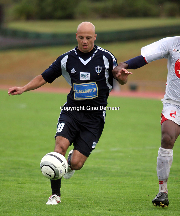 Grant young for Auckland up against George Suri  after Auckland beat Waitakere United in the NZFC Round 21 soccer match and secured the NZFC Minor Premiership at Trusts Stadium, Waitakere on Sunday 26 March 2006. Auckland City won the match 2-1. Photo: Gino Demeer/PHOTOSPORT