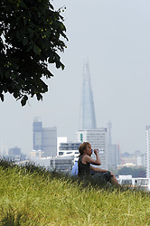 © Licensed to London News Pictures. 24/06/2014. A woman sits in the shade of a tree. Greenwich Park sunny weather, today 24th June 2014. Byline:Grant Falvey/LNP