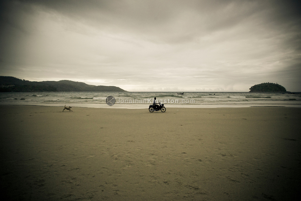 A man rides his motorcycle on Kata Noi beach while his dog chases him, Phuket, Thailand.