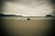 A man rides his motorcycle on Kata Noi beach while his dog chases him, Phuket, Thailand.