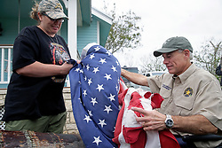 August 28, 2017 - Rockport, Texas, U.S. - BRIDGET BRUNDRETT presents a flag recovered from city hall after it had flown through Hurricane Harvey as Governor GREG ABBOTT visits Rockport. (Credit Image: © Tom Reel/San Antonio Express-News via ZUMA Wire)