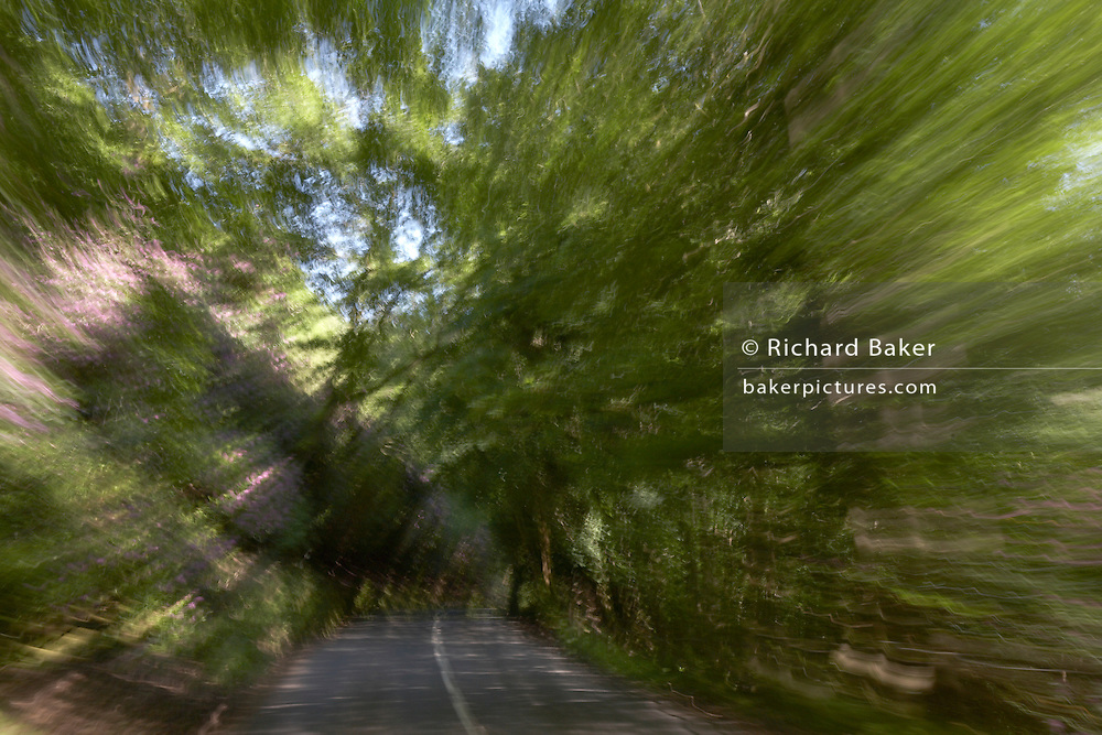 Seen through a car windscreen, the open road blurs past showing speed and freedom on Exmoor, Devon England.