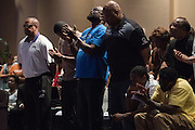 Adrian Taylor (blue) worships during a memorial service for his son Christian Taylor at Cornerstone Baptist Church in Arlington, Texas on August 12, 2015. (Cooper Neill for The New York Times)