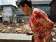 16 OCTOBER 2015 - BANGKOK, THAILAND:  A woman walks past a home that was destroyed in the Wat Kalayanamit neighborhood. Fifty-four homes around Wat Kalayanamit, a historic Buddhist temple on the Chao Phraya River in the Thonburi section of Bangkok, are being razed and the residents evicted to make way for new development at the temple. The abbot of the temple said he was evicting the residents, who have lived on the temple grounds for generations, because their homes are unsafe and because he wants to improve the temple grounds. The evictions are a part of a Bangkok trend, especially along the Chao Phraya River and BTS light rail lines. Low income people are being evicted from their long time homes to make way for urban renewal.   PHOTO BY JACK KURTZ
