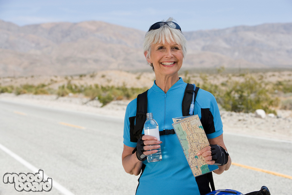 Senior woman holding map and water bottle