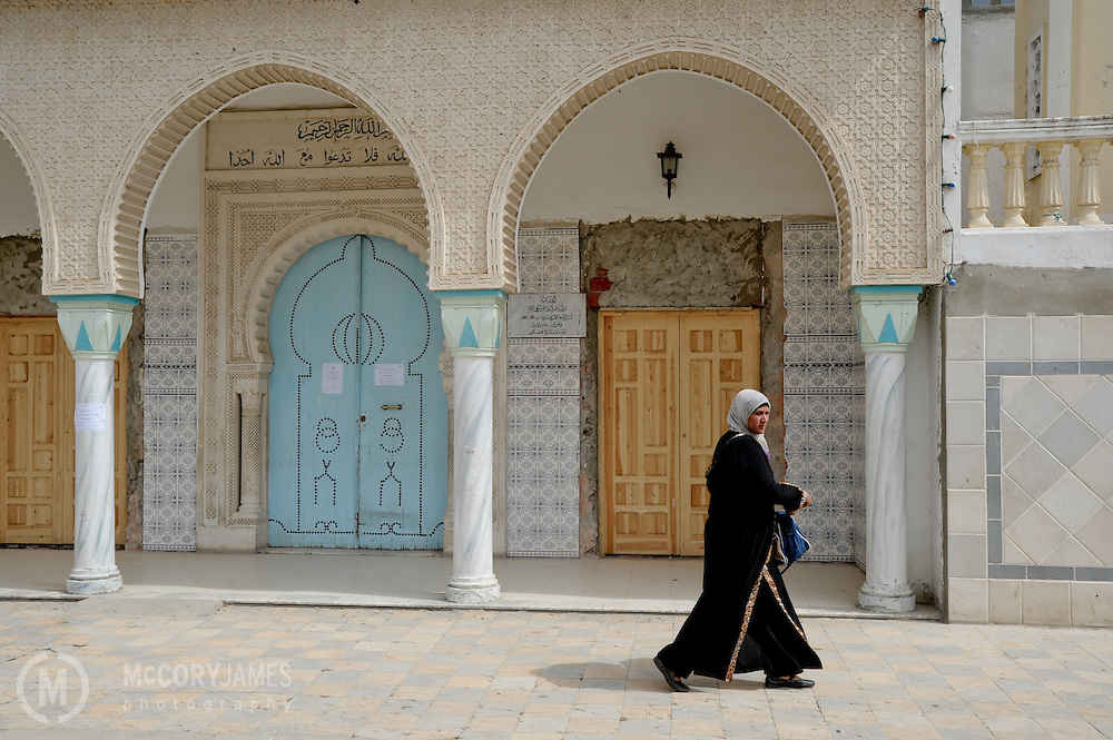 A woman walks in front of the local mosque in Jen Douba, Tunisia