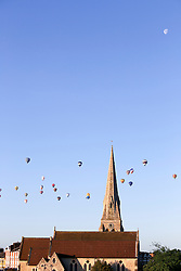 © Licensed to London News Pictures. 07/06/2015. London, UK. Hot air balloons rise over a church in Blackheath south east London on a summer morning. Photo credit : Stu Mayhew/LNP