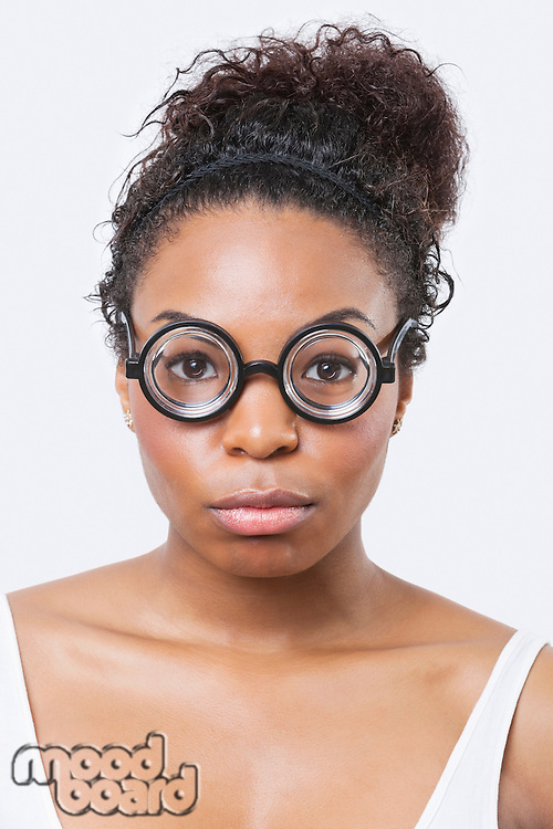 Close-up portrait of African American young woman wearing novelty glasses over white background