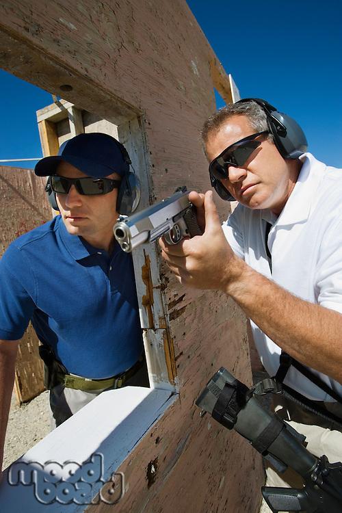Instructor assisting man aiming hand gun at firing range