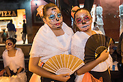 Young women dressed as La Calavera Catrina during the Day of the Dead festival in the Plaza Civica October 28, 2016 in San Miguel de Allende, Guanajuato, Mexico. The week-long celebration is a time when Mexicans welcome the dead back to earth for a visit and celebrate life.
