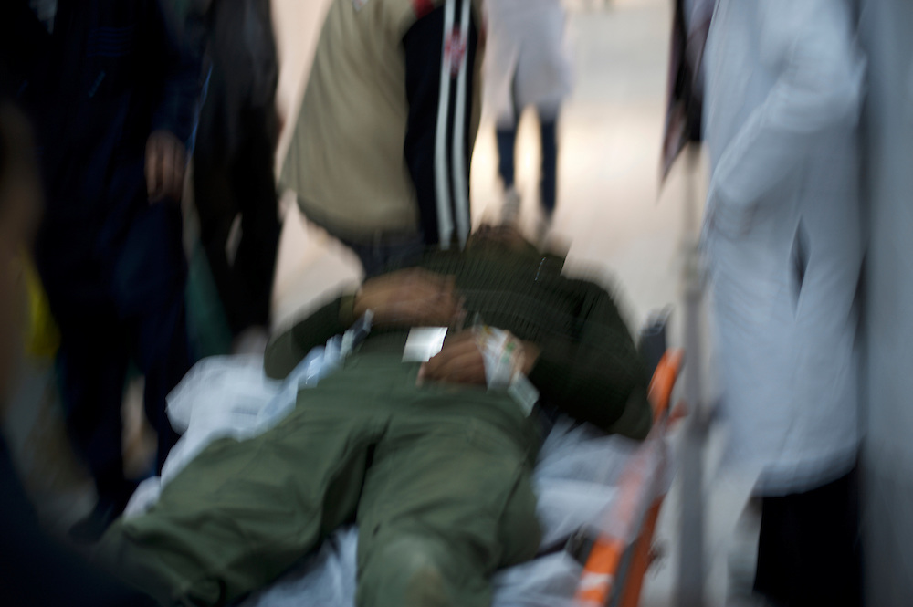 A wounded rebel fighter is rushed into the emergency room at the hospital in Ajdabiya.
