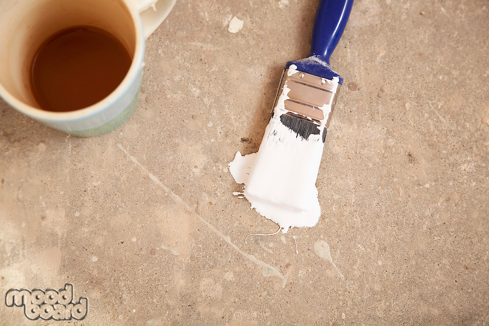 Coffee mug and paintbrush lying on floor view from above